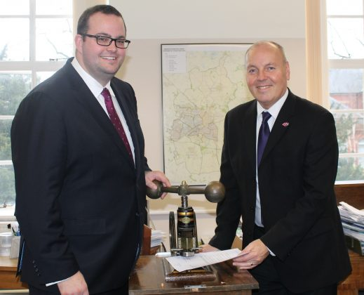 Cllr Toby Elliott, Swindon Borough Council's Cabinet Member for Strategic Planning and Sustainability (left) with Swindon Borough Council's Chief Executive John Gilbert using the Council's embossing machine to affix the Council's seal to the Wichelstowe Joint Venture documentation.