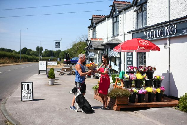Janice Harding sells flowers to Trevor Mullineaux outside the Ye Old 3 pub.